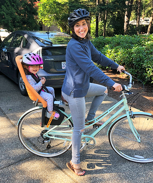 Allie Coombs on bicycle with child